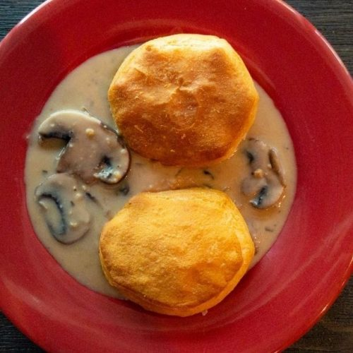 vegan biscuits and gravy on a red plate